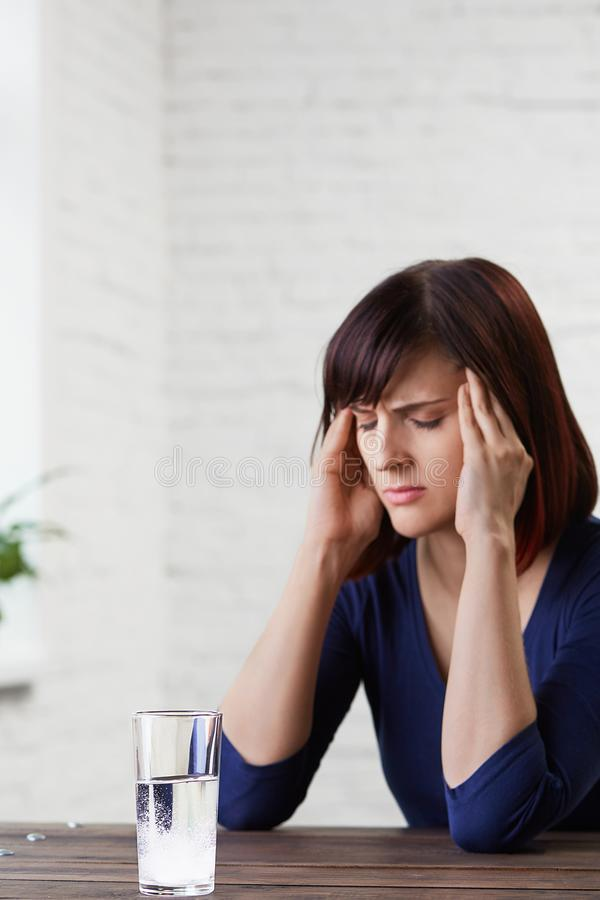 Jonge vrouw die aan sterke hoofdpijn lijden, vingers houden aan haar tempels en ogen van pijn sluiten, die geneeskunde prepairing stock afbeeldingen