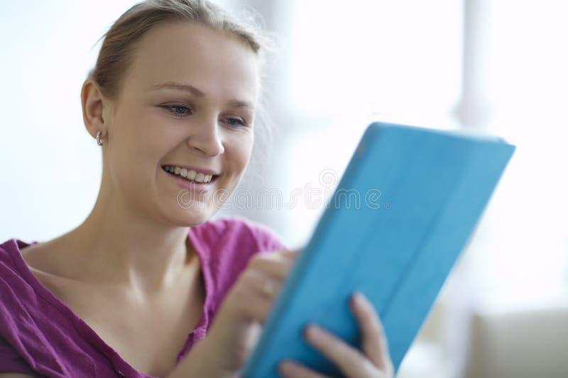Jonge vrouw die aangezien zij brandingen Internet glimlachen royalty-vrije stock foto