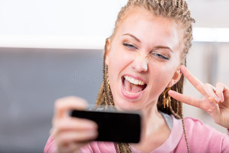 Jonge vrouw die aangezien zij een selfie neemt toejuichen stock afbeeldingen