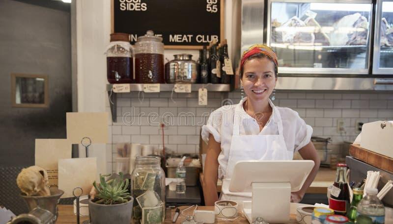 Jonge vrouw die achter de teller in een slagerij wachten stock afbeelding