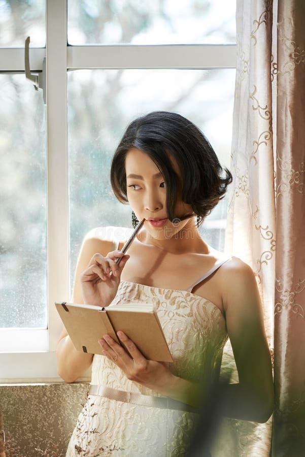Jonge vrouw die in agenda schrijven royalty-vrije stock foto's