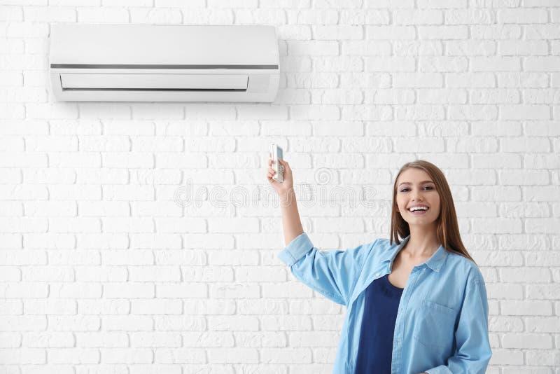 Jonge vrouw die airconditioner inschakelen stock foto