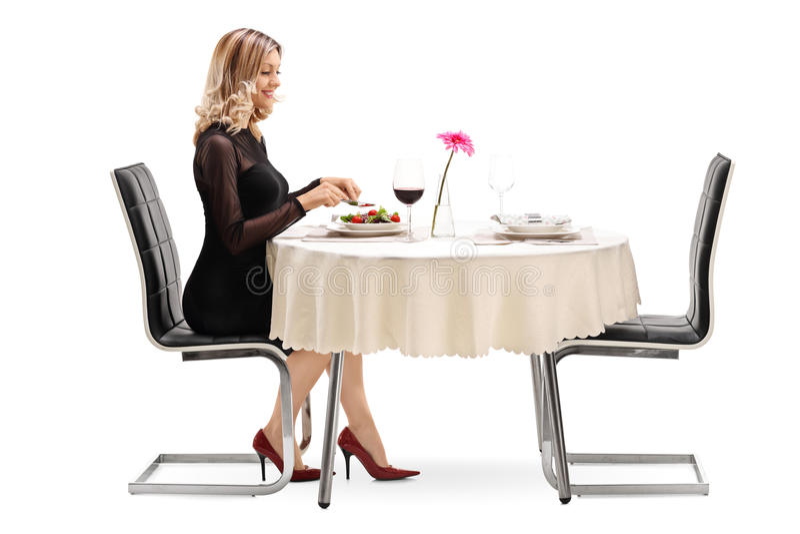 Jonge vrouw die alleen diner eten stock fotografie