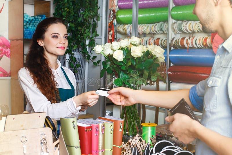 Jonge vrouw die als bloemist werken die creditcard geven aan klant royalty-vrije stock foto's