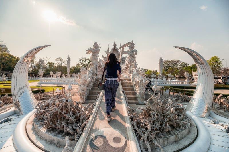 Jonge vrouw die in architectuur en kunst van witte tempel in Wat Rong Khun, Chiang Rai lopen stock foto's