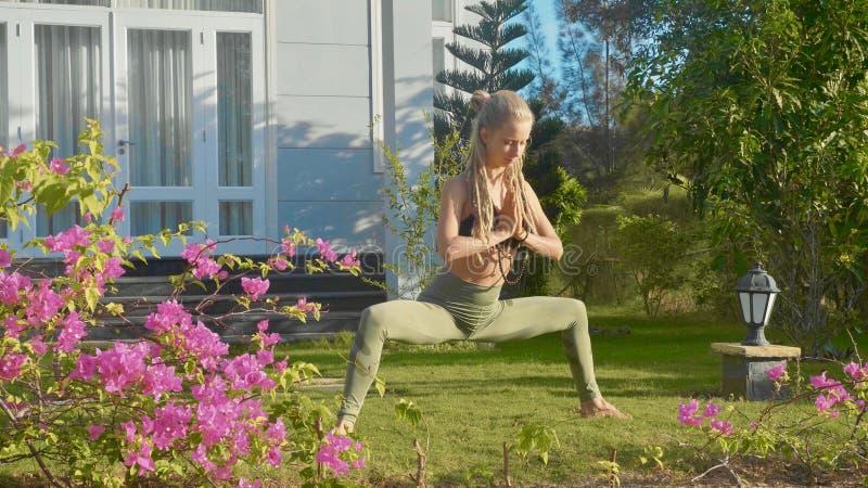 Jonge vrouw die asanayoga doen bij de binnenplaats van haar huis met mooie tuin stock foto