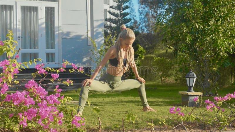 Jonge vrouw die asanayoga doen bij de binnenplaats van haar huis met mooie tuin royalty-vrije stock foto