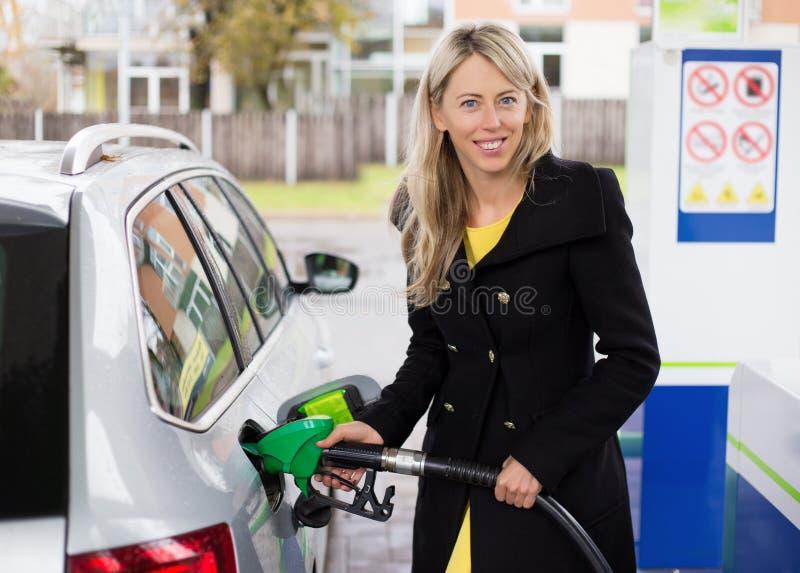Jonge vrouw die auto in benzinestation opnieuw vullen stock fotografie