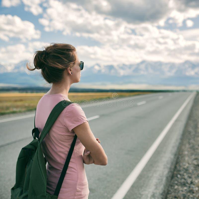 Jonge vrouw die backpacker op weg lopen royalty-vrije stock fotografie