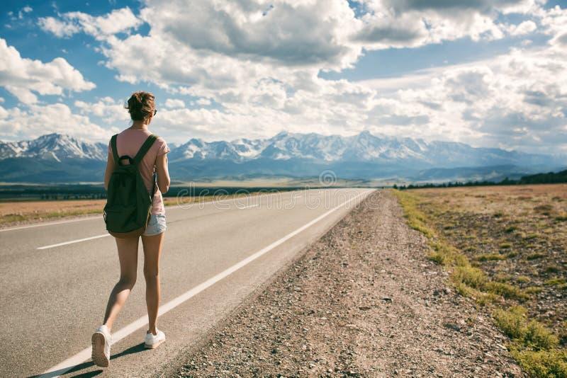 Jonge vrouw die backpacker op weg lopen stock foto's