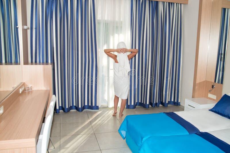 Jonge vrouw die in badhanddoek uit het venster in de ruimte kijken Ontwaken in de ochtend royalty-vrije stock afbeelding