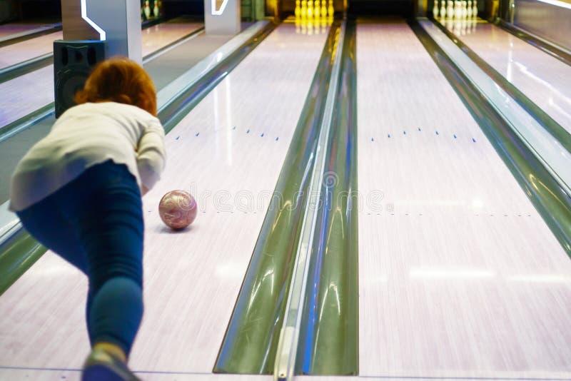 Jonge vrouw die bal in kegelenclub werpen royalty-vrije stock fotografie