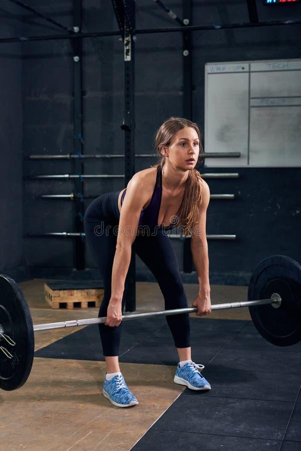 Jonge Vrouw die Barbell in Gymnastiek opheffen royalty-vrije stock afbeeldingen