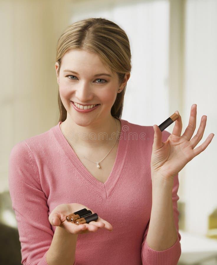 Jonge Vrouw die Batterijen toont royalty-vrije stock afbeelding