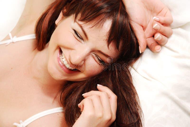 Jonge vrouw die in bed lacht royalty-vrije stock foto's