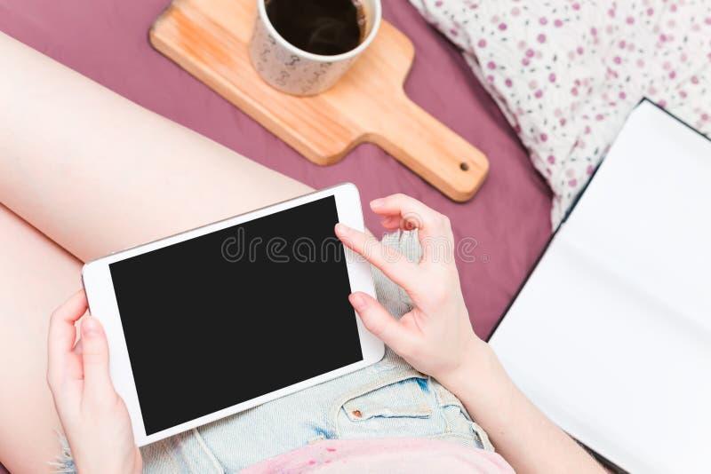 Jonge vrouw die in bed met digitale tablet liggen royalty-vrije stock afbeelding
