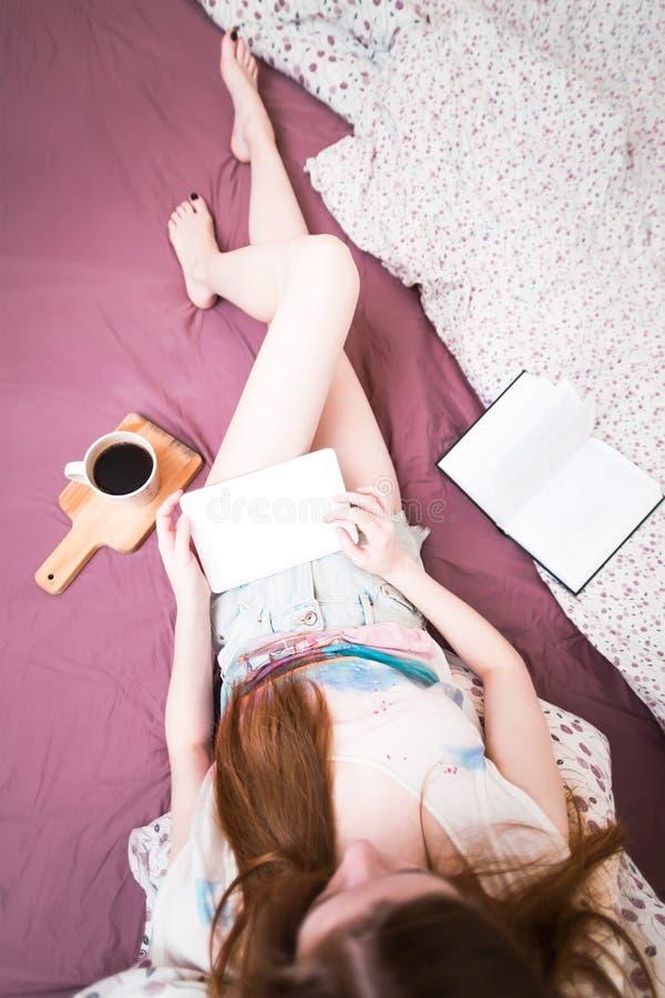 Jonge vrouw die in bed met digitale tablet liggen stock foto