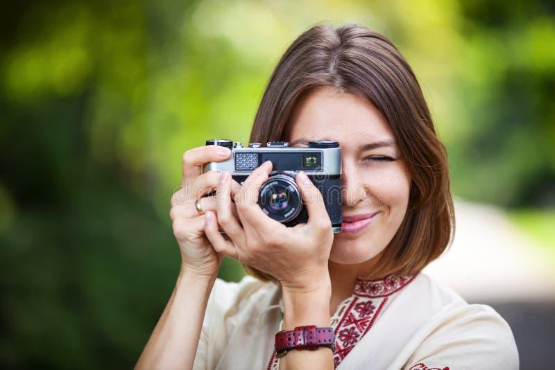 Jonge vrouw die beeld met retro camera nemen royalty-vrije stock fotografie