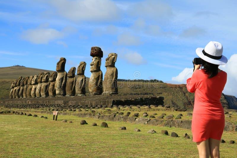Jonge vrouw die beelden van de beroemde Moai-standbeelden nemen in Ahu Tongariki op Pasen-Eiland stock afbeeldingen