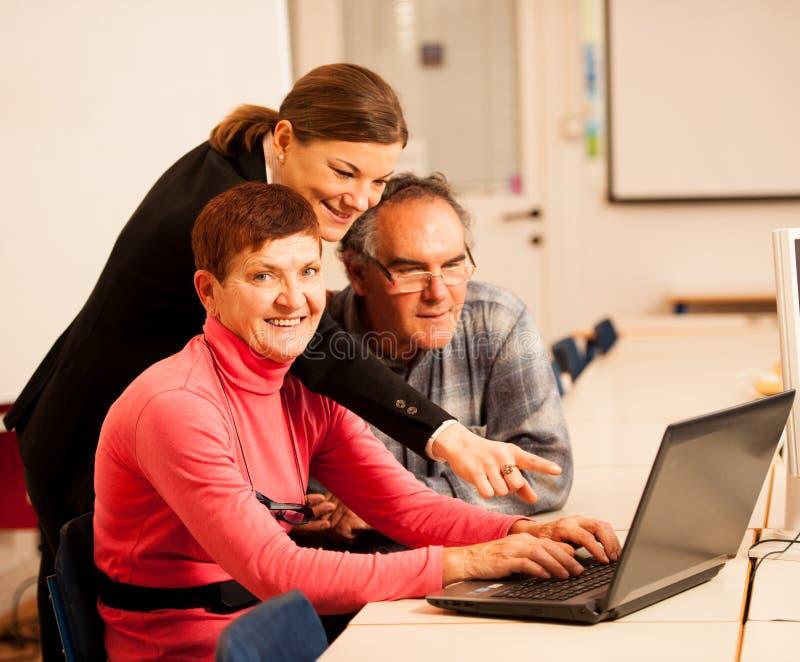 Jonge vrouw die bejaard paar van computervaardigheden onderwijzen Intergen stock afbeelding