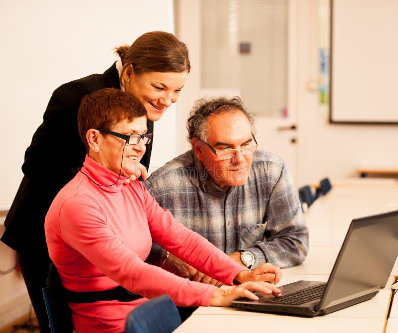 Jonge vrouw die bejaard paar van computervaardigheden onderwijzen Intergen stock fotografie