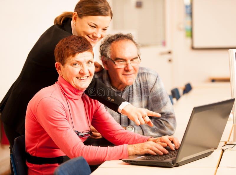 Jonge vrouw die bejaard paar van computervaardigheden onderwijzen Intergen royalty-vrije stock afbeelding