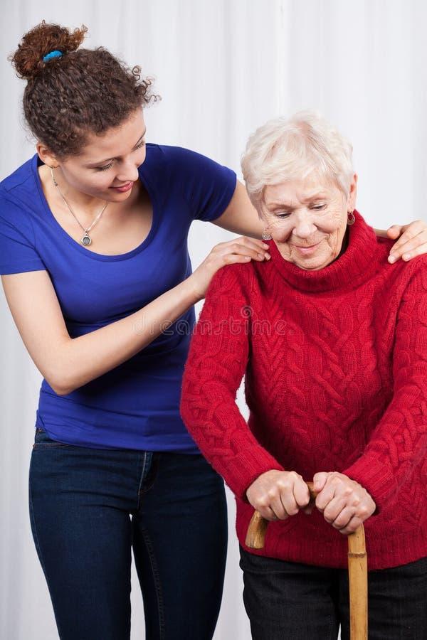Jonge vrouw die bejaarde dame helpen stock fotografie
