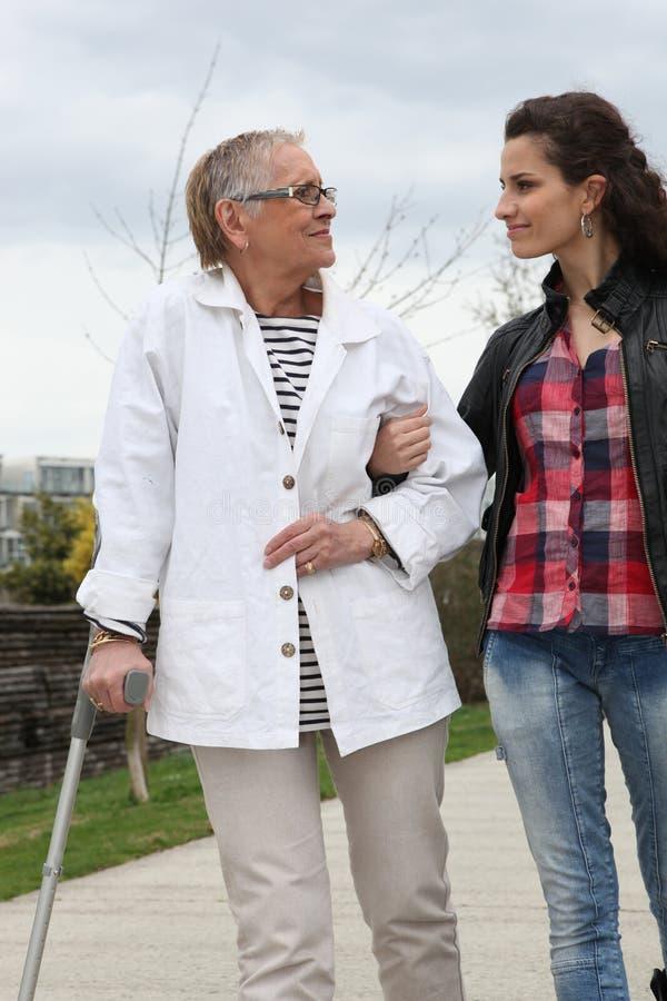 Jonge vrouw die bejaarde persoon helpt stock foto