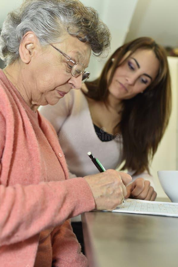 Jonge vrouw die bejaarden helpen die kruiswoordraadsels doen stock fotografie