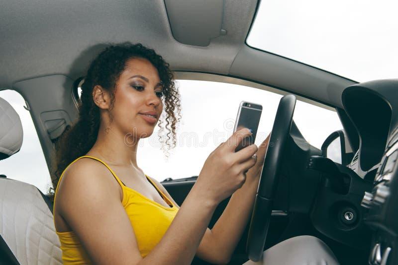 Jonge Vrouw die Berichten verzenden terwijl het Drijven Jonge vrouw die aan haar smartphone kijken terwijl het drijven van auto royalty-vrije stock foto's