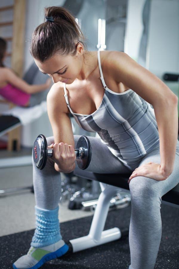 Jonge vrouw die Bicepsenoefening doen stock afbeeldingen