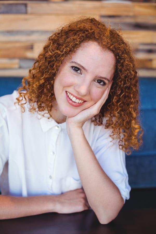 Jonge vrouw die bij camera glimlachen stock afbeeldingen