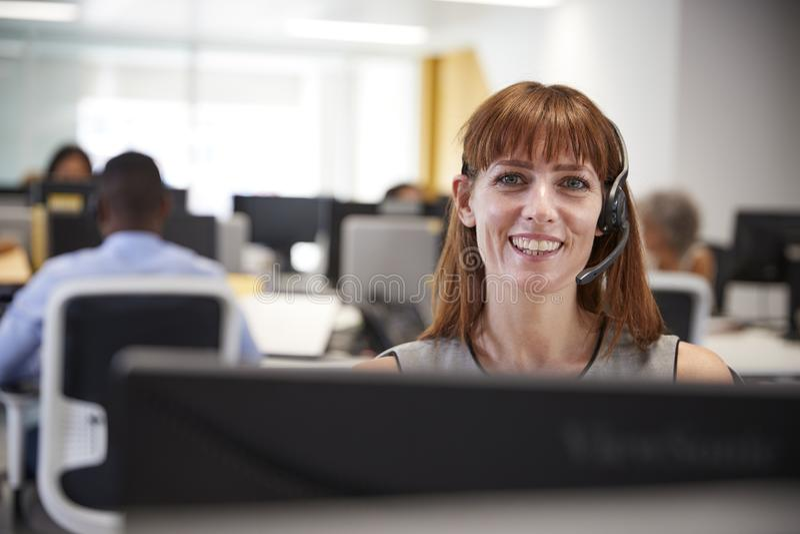 Jonge vrouw die bij computer met hoofdtelefoon in bezig bureau werken royalty-vrije stock afbeelding