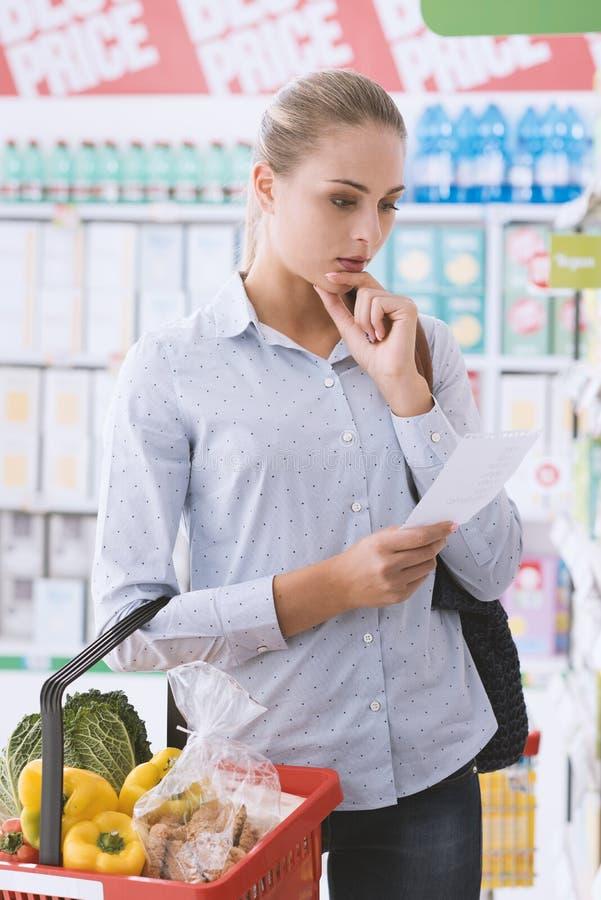 Jonge vrouw die bij de supermarkt winkelen stock foto