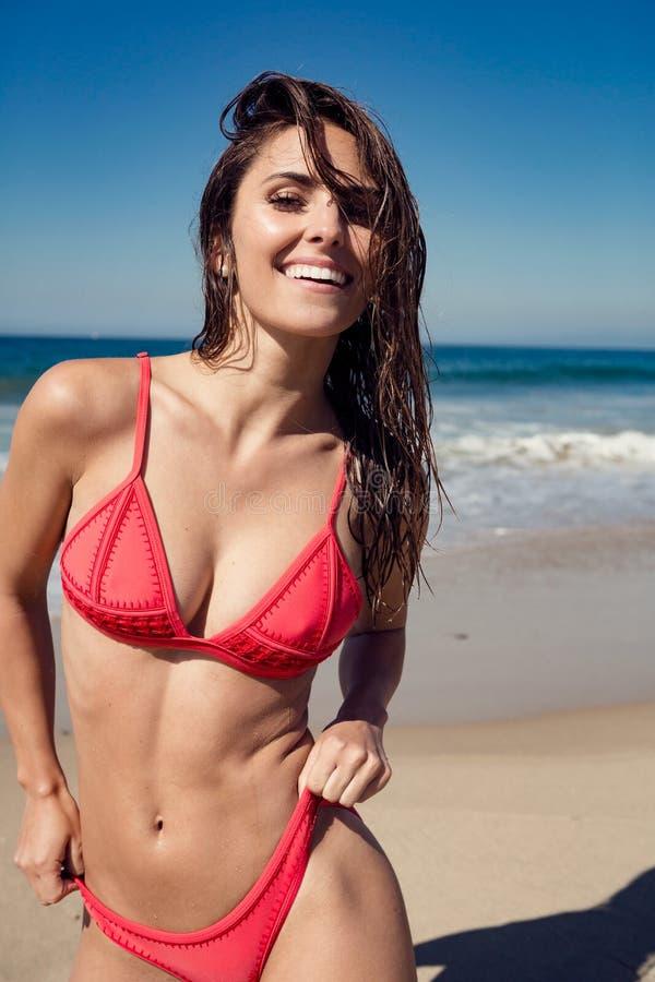 Jonge vrouw die bij het strand glimlachen stock fotografie