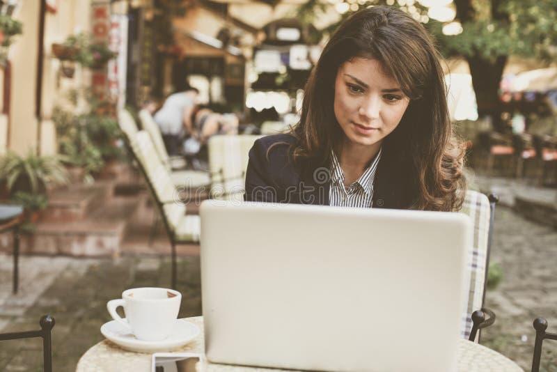 Jonge vrouw die bij koffie aan laptop werken Sluit omhoog royalty-vrije stock afbeelding