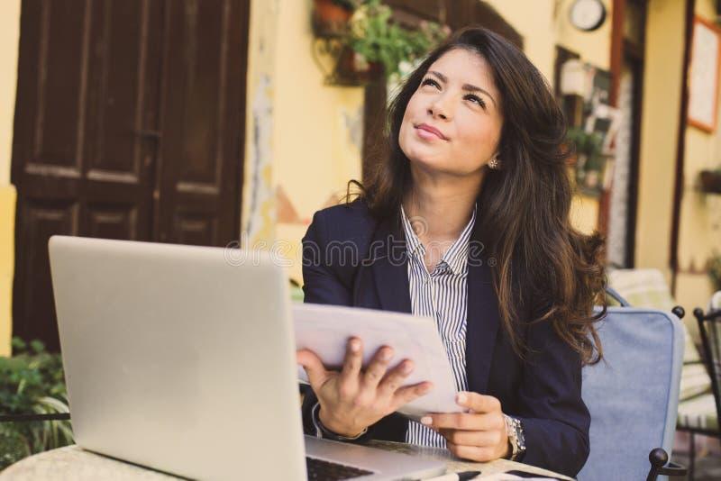 Jonge vrouw die bij koffie, controledocumenten werken royalty-vrije stock fotografie