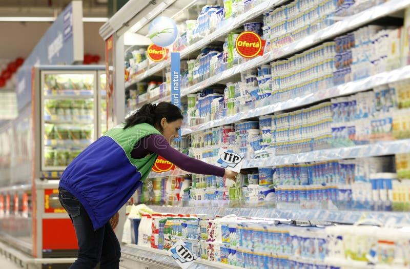 Jonge vrouw die bij supermarkt winkelt royalty-vrije stock afbeelding