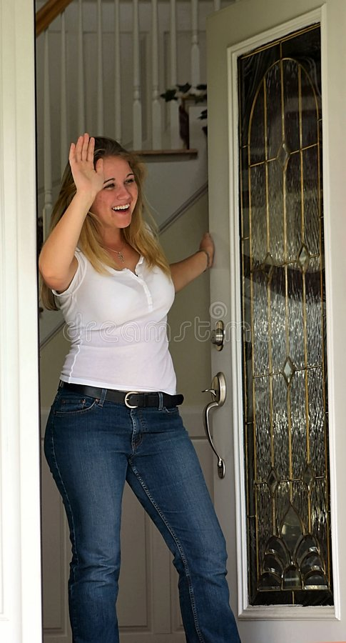 Jonge vrouw die bij voordeur golft royalty-vrije stock foto