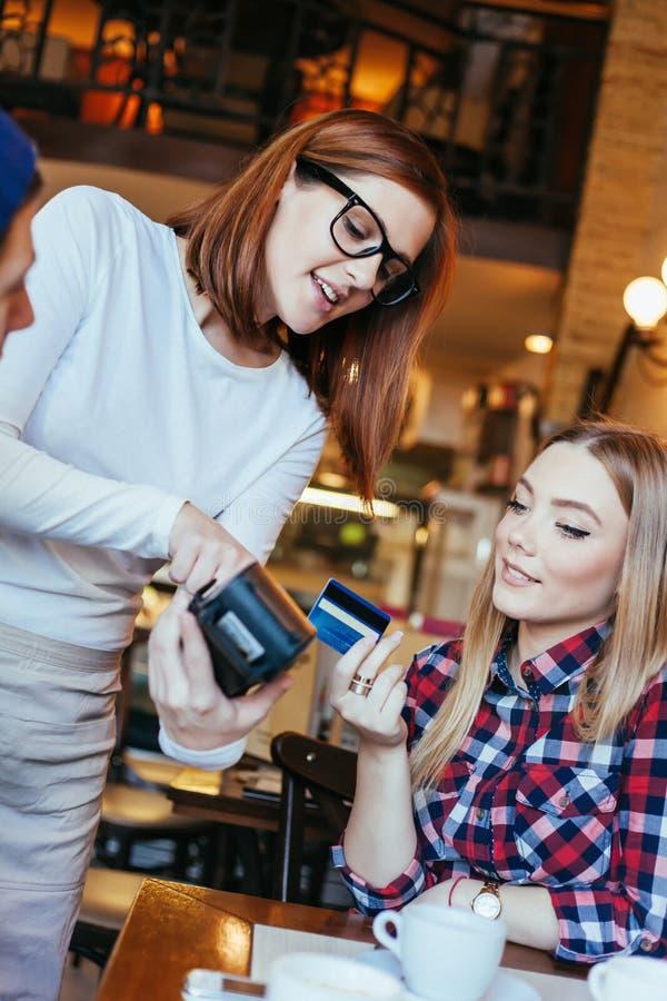 Jonge Vrouw die Bill By Credit Card betalen stock afbeelding