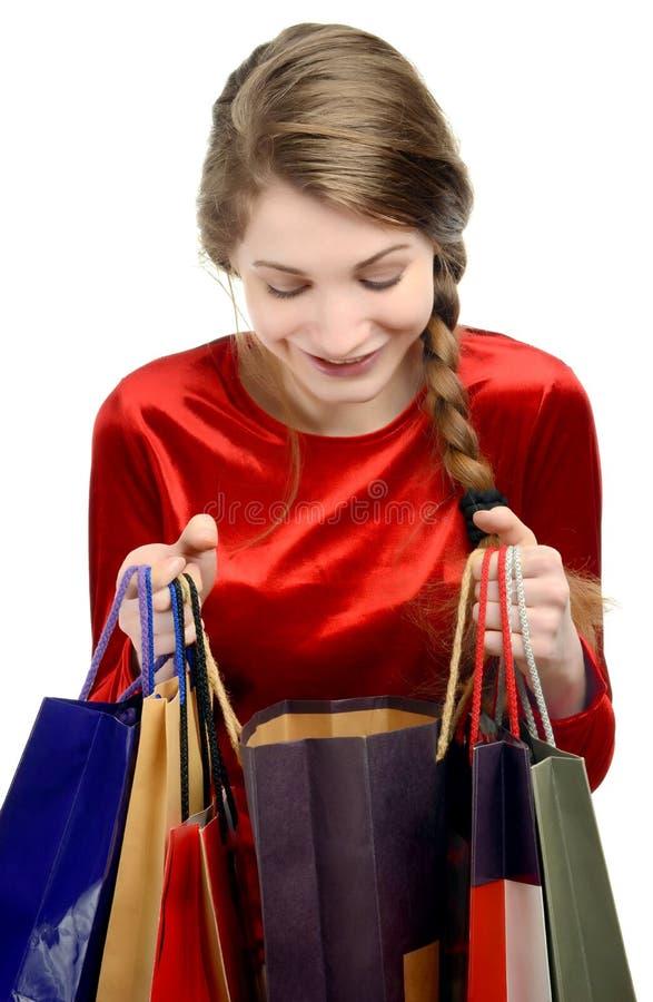 Jonge vrouw die binnen de het winkelen zakken kijken. royalty-vrije stock fotografie