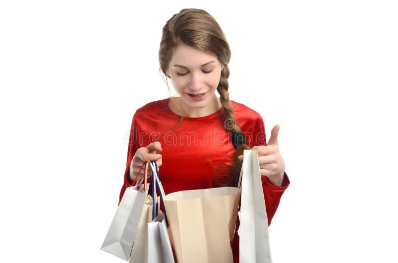 Jonge vrouw die binnen de het winkelen zakken kijken. stock fotografie