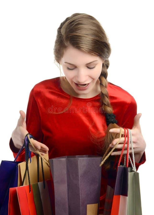 Jonge vrouw die binnen de het winkelen zakken kijken. stock afbeelding