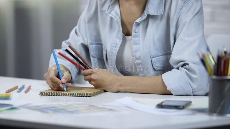Jonge vrouw die binnenland ontwerpen, freelancer doend werk, die met potloden het kleuren royalty-vrije stock afbeelding