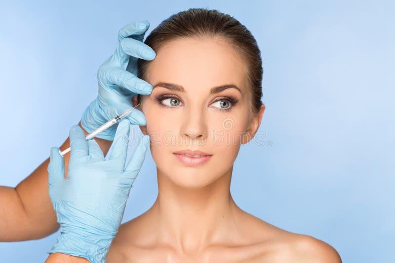 Jonge vrouw die BOTOX® ontvangen; injecties stock foto's