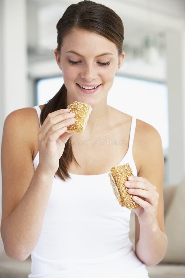 Jonge Vrouw die Bruin Broodje eet royalty-vrije stock fotografie