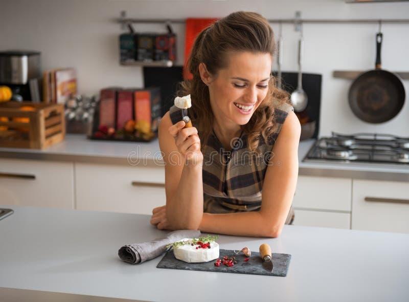 Jonge vrouw die camembert eten stock afbeeldingen