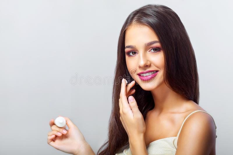 Jonge vrouw die camera met gezichtsvochtinbrengende crème dichtbij ogen bekijken B stock afbeeldingen