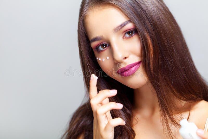 Jonge vrouw die camera met gezichtsvochtinbrengende crème dichtbij ogen bekijken B royalty-vrije stock foto's