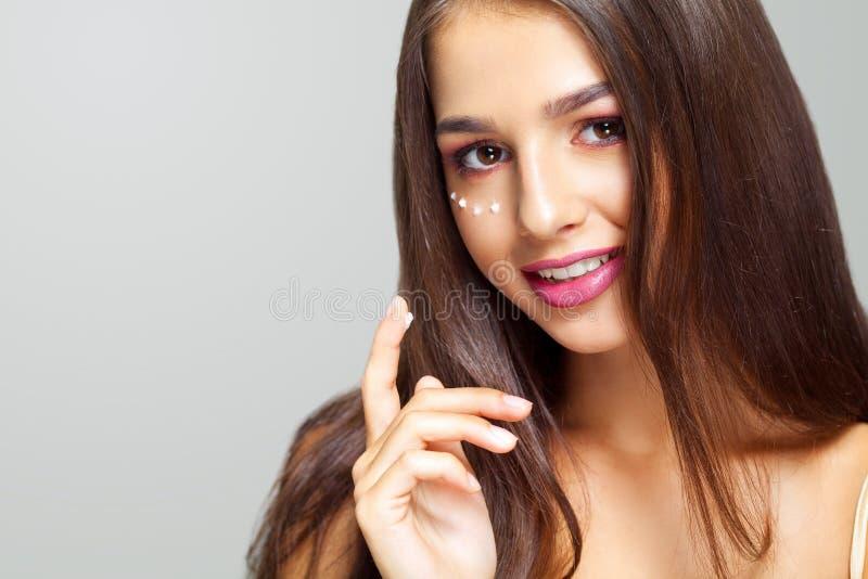 Jonge vrouw die camera met gezichtsvochtinbrengende crème dichtbij ogen bekijken B stock fotografie